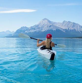 woman on blue water lake in kayak