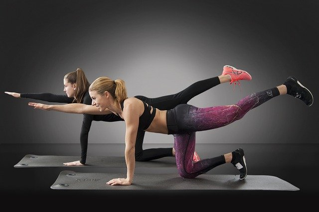 image of two women doing leg extensions on yoga mat