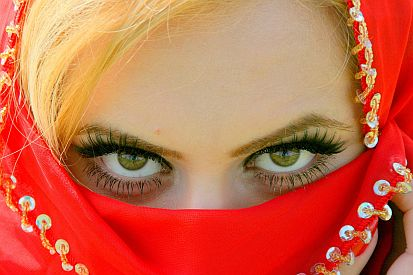 womans brown eyes with red vail