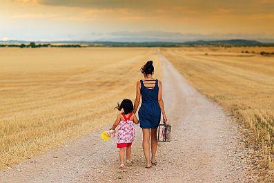 girl and woman walking down dirt road