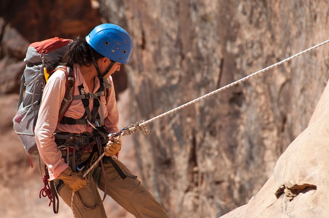 woman repelling down mountain