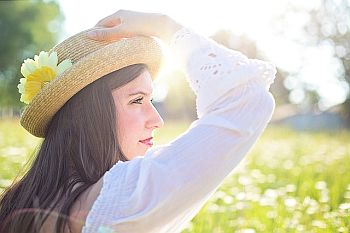 woman wearing hat in field with sun behind her